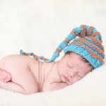newborn baby boy sleeping in a hand knitted striped hat photographed by San Francisco Bay Area and Santa Barbara baby photographer Sarka Photography
