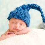 newborn baby boy sleeping in a hand knitted blue hat photographed by San Francisco Bay Area and Santa Barbara baby photographer Sarka Photography