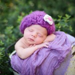 newborn baby girl sleeping in a bucket wearing a purple knitted hat photographed by San Francisco Bay Area and Santa Barbara baby photographer Sarka Photography