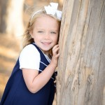 little girl smiling by a tree photographed by Santa Barbara and San Francisco Bay area photographer Sarka Photography