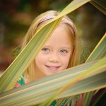 little girl peaking through leaves photographed by Santa Barbara and San Francisco Bay area photographer Sarka Photography