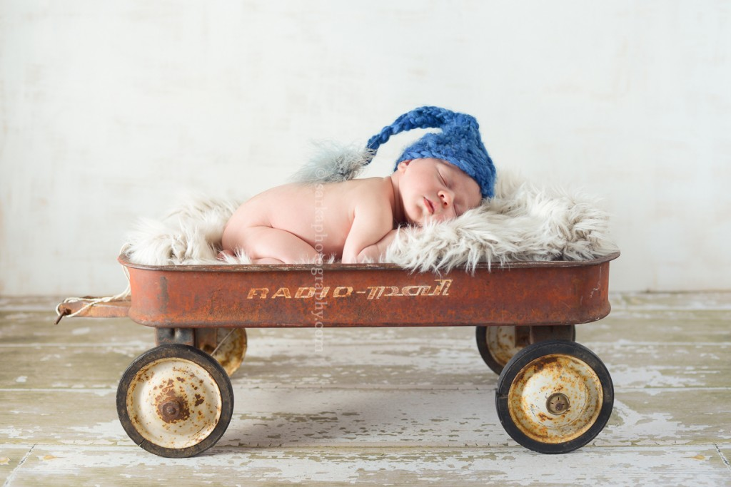 newborn baby boy sleeping in a vintage wagon by Marin baby photographer Sarka Photography