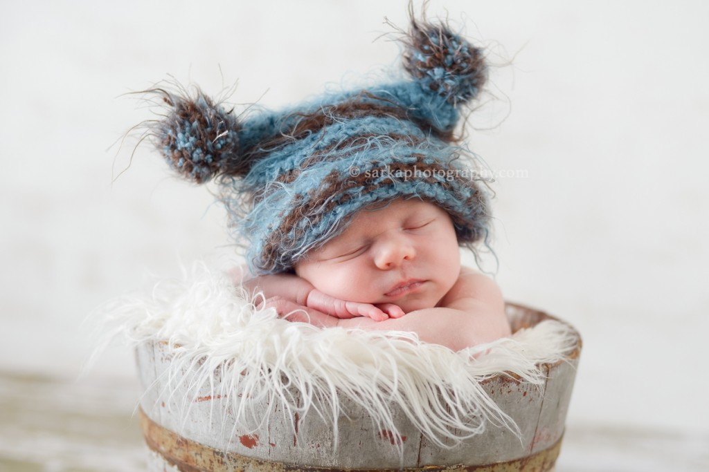 newborn baby boy wearing a hand knitted hat sleeping in a vintage bucket photographed by Marin baby photographer