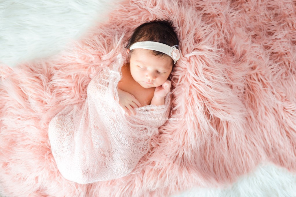newborn baby girl swaddled in a pink hand knitted wrap photographed by Santa Barbara and San Jose Baby photographer Sarka Photography
