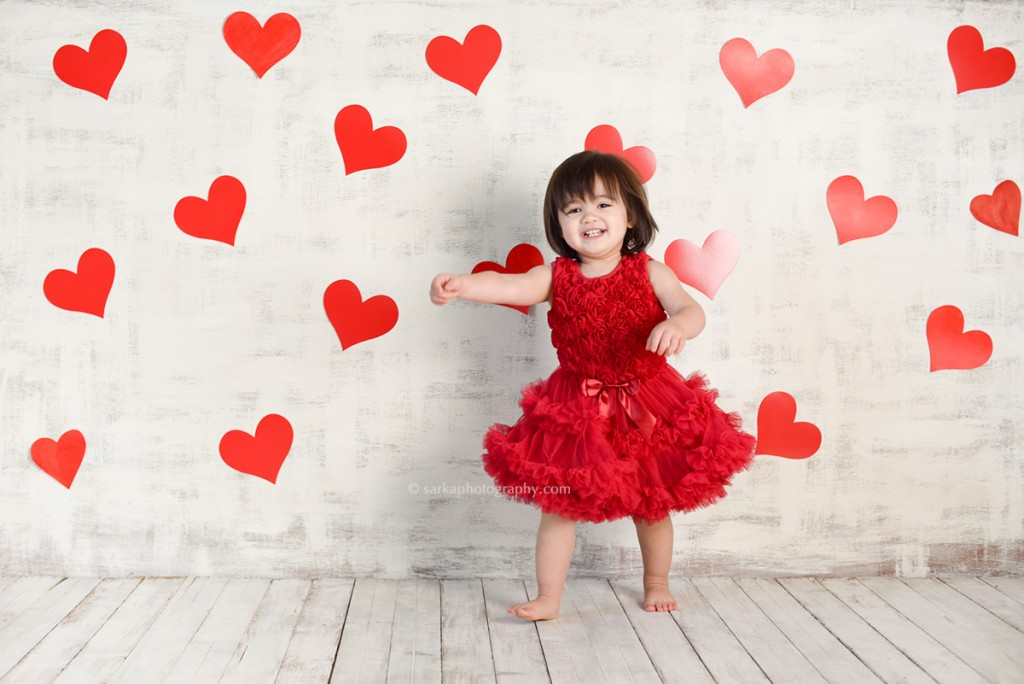 toddler girl in a red chiffon dress surrounded by hearts for Valentine's day photographed by Santa Barbara baby and children photographer Sarka photography