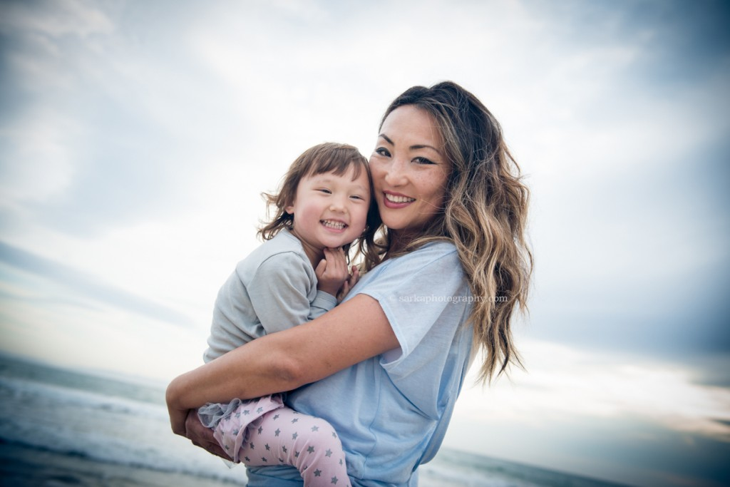 young mom holding her daughter on the beach little girl in her moms arms on the beach at sunset photographed by Santa Barbara children and family photographer by Sarka Photography