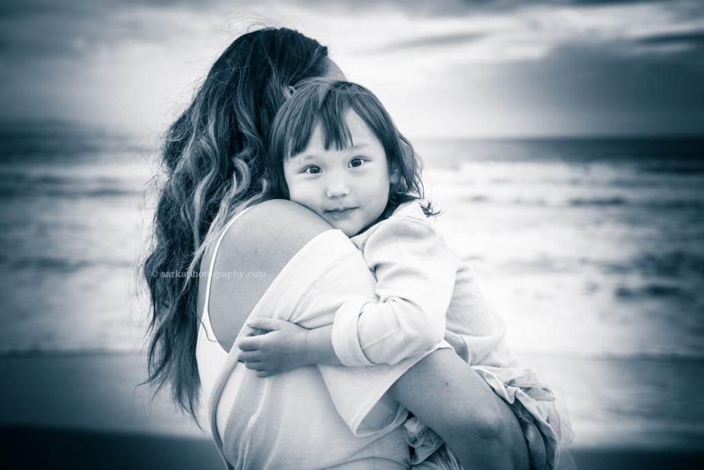 little girl in her moms arms on the beach at sunset photographed by Santa Barbara children and family photographer by Sarka Photography
