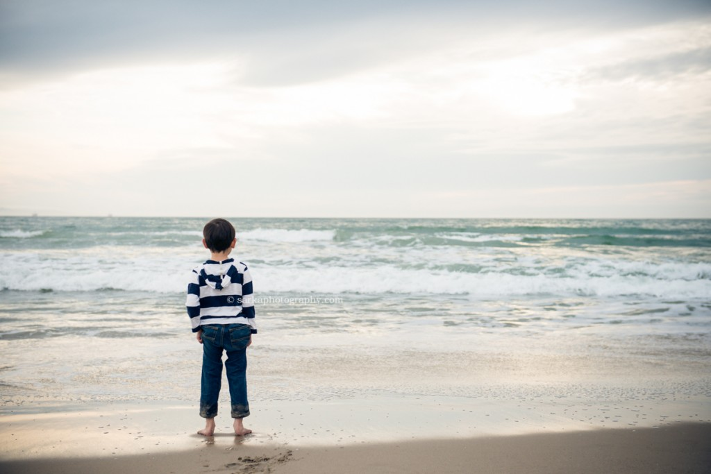 little boy looking out at the ocean during sunset photographed by Santa Barbara children and family photographer by Sarka Photography