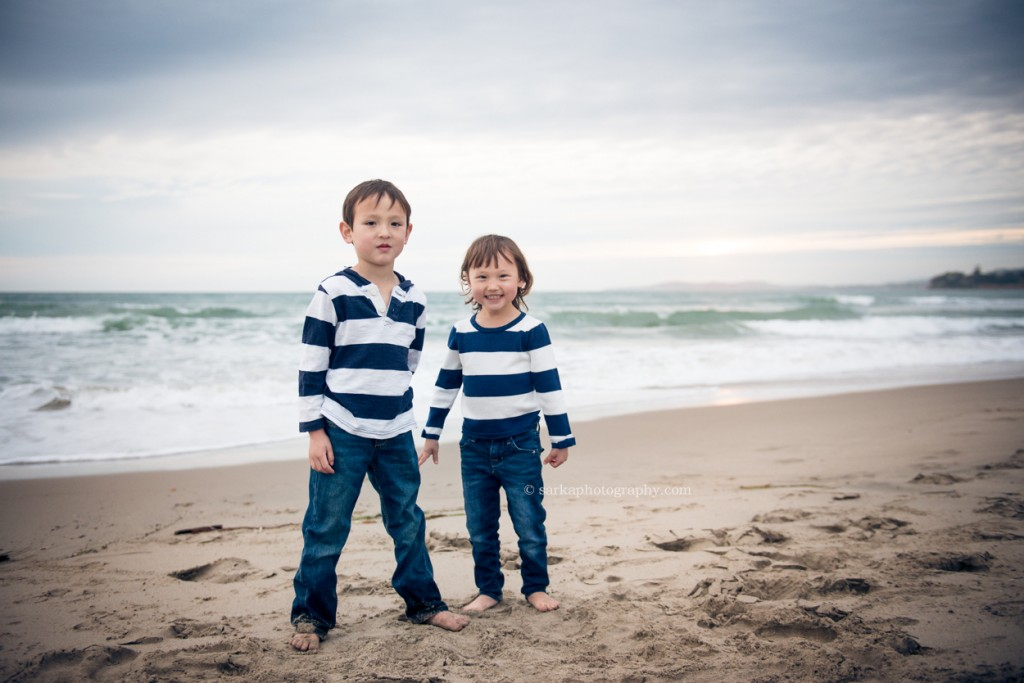 siblings playing on the beach in Santa Barbara during family and children photo session by Sarka Photography