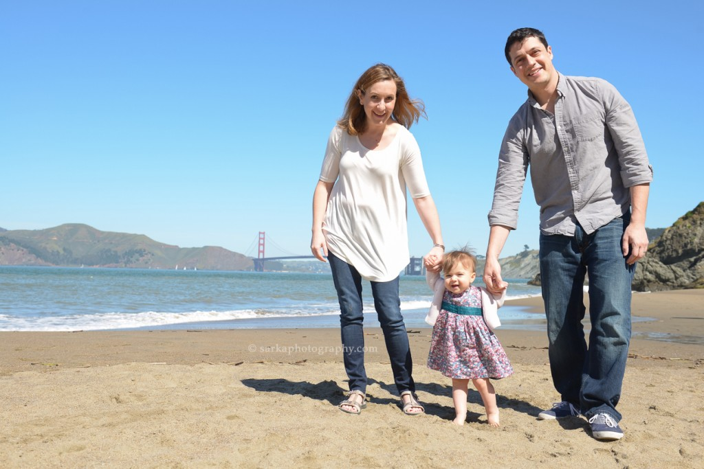young parents holding walking on the beach in San Francisco with their one year old baby girl photographed by San Francisco and Santa Barbara baby photographer Sarka