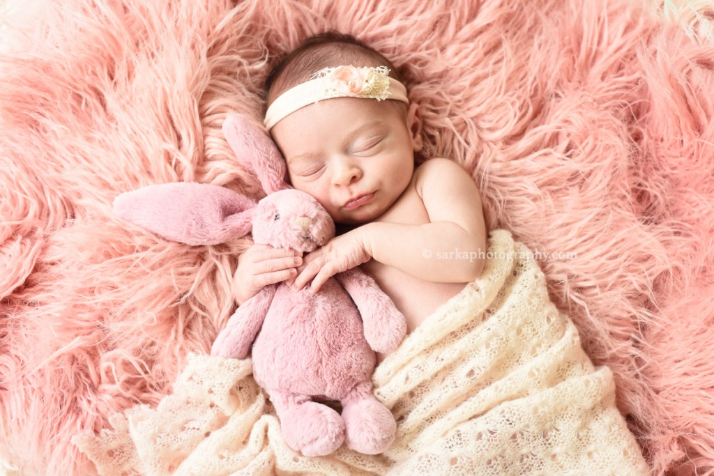 newborn baby girl sleeping and holding a stuffed animal pink bunny photographed by San Francisco and Santa Barbara newborn baby photographer Sarka photography