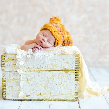 newborn baby girl sleeping in a rustic wooden box wearing a hand knitted hat photo by Santa Barbara Thousand Oaks Malibu baby newborn and family photographer Sarka photography