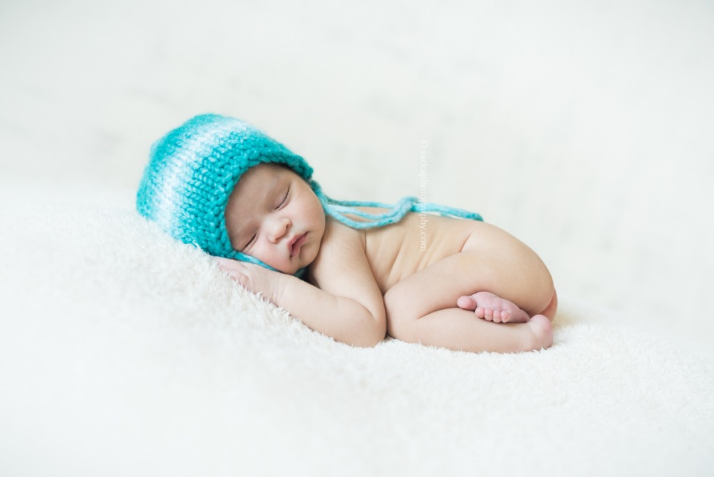 newborn baby boy sleeping in a hand knitted hat by Santa Barbara Montecito newborn photographer sarkaphotography