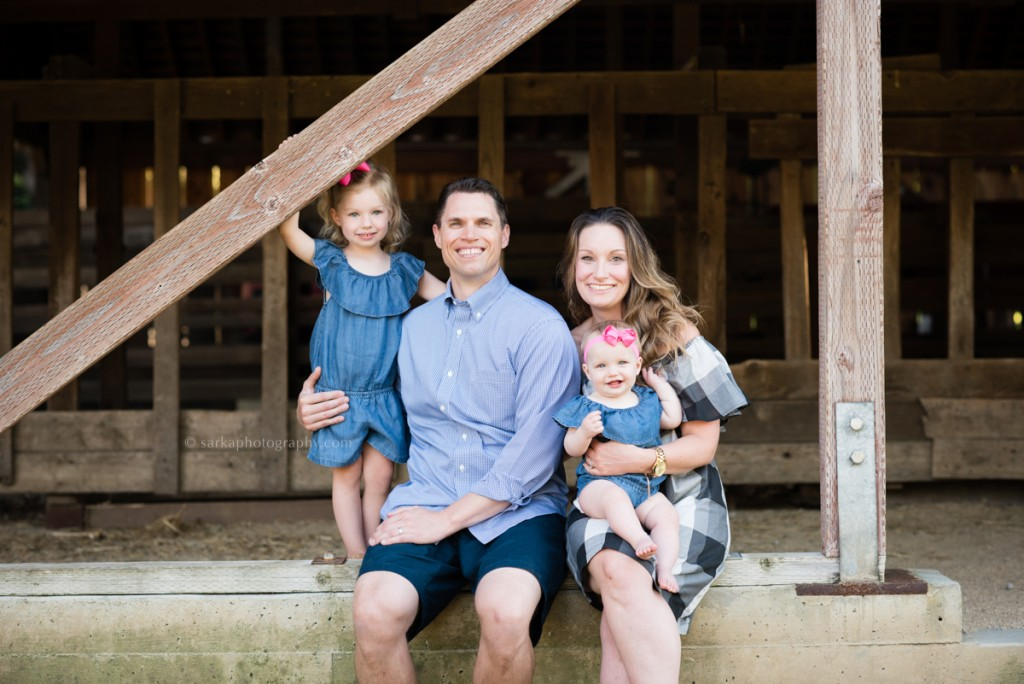 family with two children sitting at a barn during their family photo session with Sarkaphotography