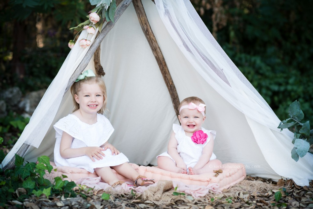 sibling daughters sitting in a flowery tent with Santa Barbara Montecito children portraits photographer sarkaphotography