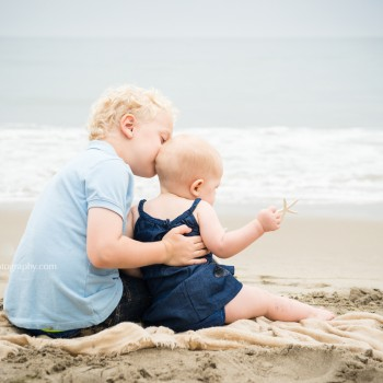 little boy kissing his younger sister sitting on a beach during their family photo session in Montecito Santa Barbara by sarkaphotography