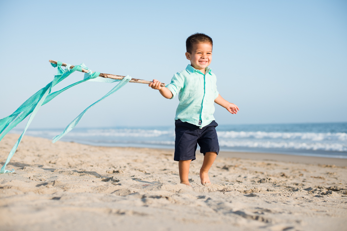 toddler boy running on a beach during his child portrait lifestyle photo session in Carpinteria by Santa Barbara children and family photographer sarkaphotography