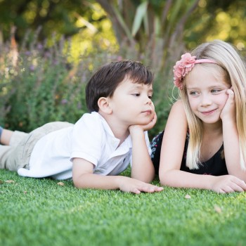 young siblings laying on a grass photographed by bay area burlingame family photographer sarkaphotography