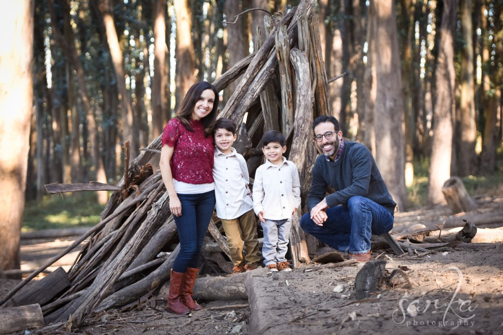 family posing in the woodsy park during their family portraits session by sarkaphotography