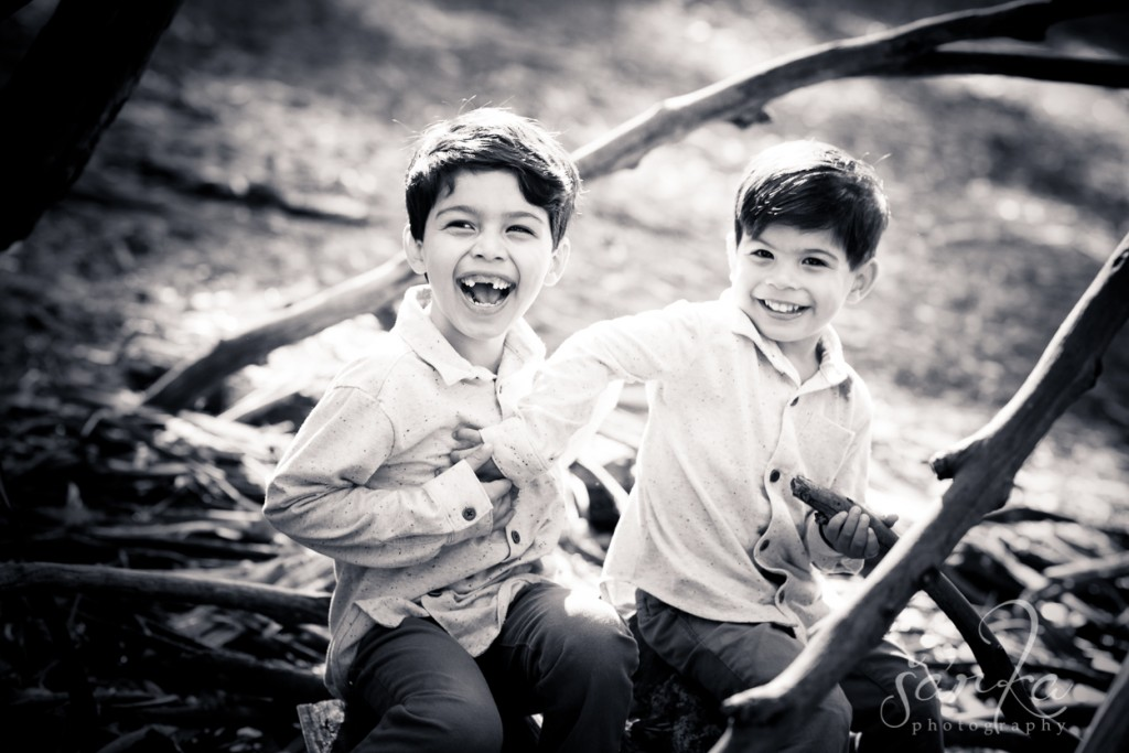 two brothers playing in the woodsy park during their family portraits session by sarkaphotography