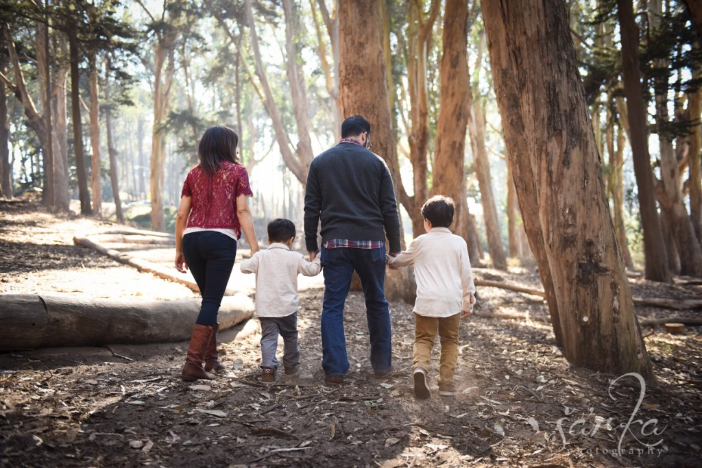 family walking in the woodsy park during their family portraits session by sarkaphotography